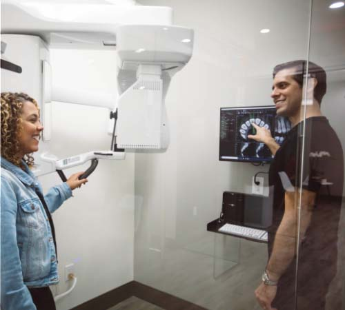 Dr. Kottar showing the state-of-the-art 3D CT scanner to a smiling patient