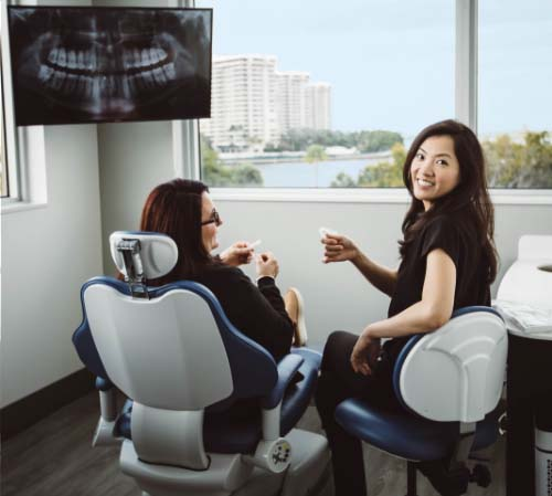Board-certified orthodontist Dr. Patricia Hong holding Invisalign trays with a patient