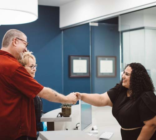 Smiling receptionist welcoming a couple to the dental office