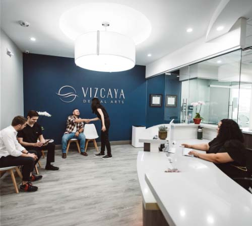 Picture of the reception area of Vizcaya Dental Arts with waiting patients being welcomed by Dr. Kottar and Dr. Hong