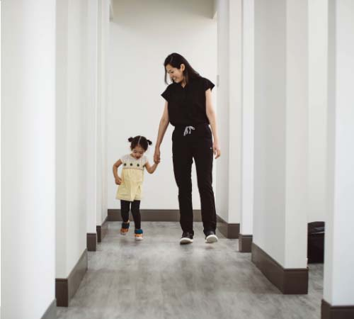 Board-certified orthodontist Dr. Hong walking down the hallway with young patient