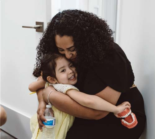 Staff member hugging a little girl