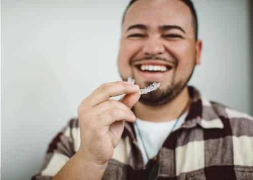 Smiling orthodontic patient holding Invisalign clear aligners