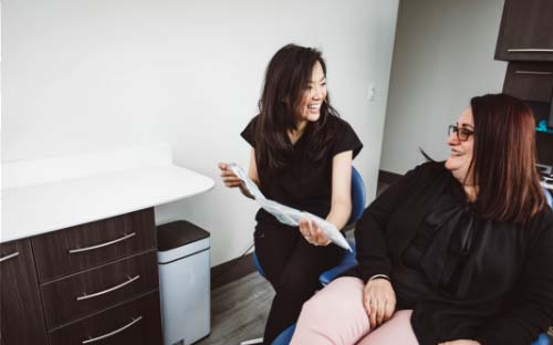 Picture of Dr. Hong with a smiling female patient showing Invisalign aligners