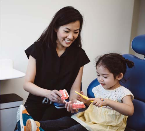 Dr. Hong watching a young patient practice brushing on a dental model