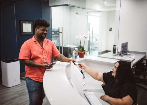 Smiling patient being welcomed to our multi-specialty dental office in Miami